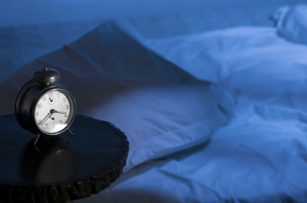 Alarm clock next to an empty bed